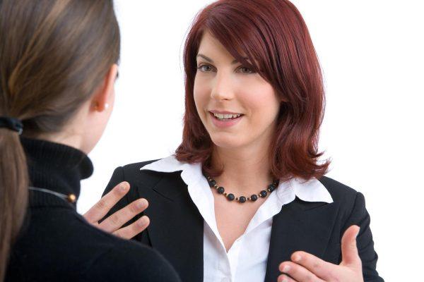 zwei junge hübsche Geschäftsfrauen besprechen etwas